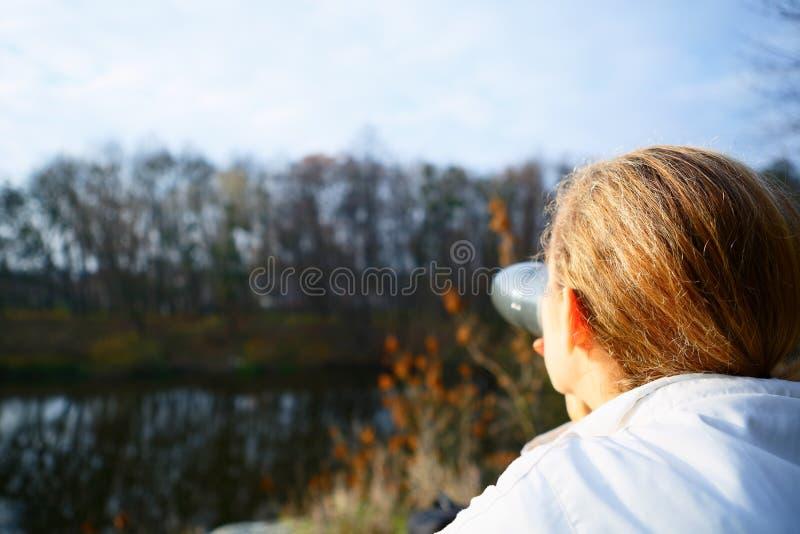 Thé potable de randonneur de femme d'un thermos sur la nature d'automne photo stock