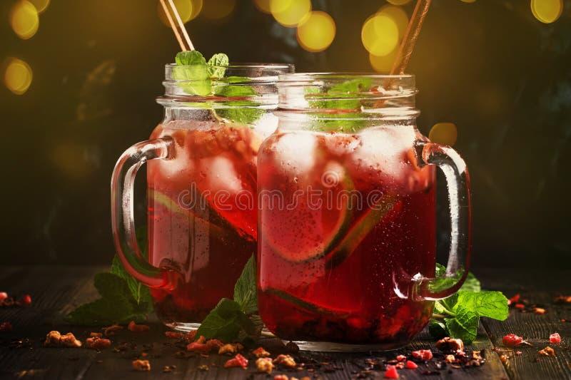 Thé rouge d'été froid avec de la glace, la chaux et la menthe, boisson non alcoolisée régénératrice dans des pots, fond foncé de  photos stock