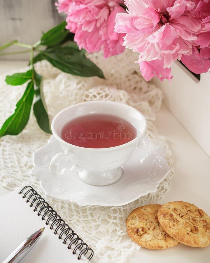 Thé rouge de baie ou de fruit dans la tasse de thé avec la pivoine photo stock