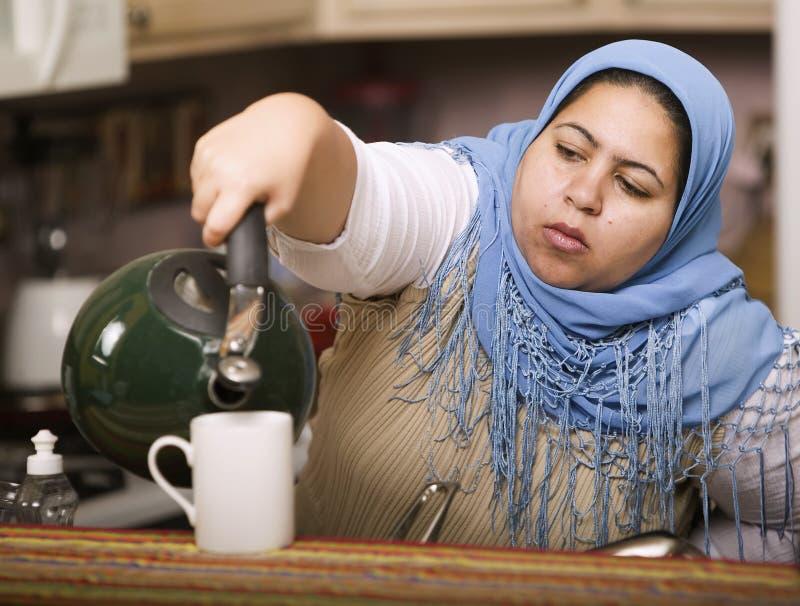 Thé se renversant de femme musulmane images libres de droits