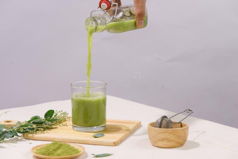 Thé vert étant renversé dans la tasse de thé en verre sur la table blanche photo stock