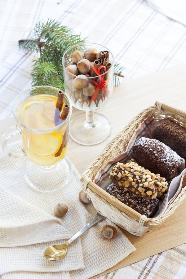 Thé vert chaud frais dans la tasse en verre avec le citron et la cannelle, les gâteaux de chocolat dans le panier et les écrous e photo libre de droits