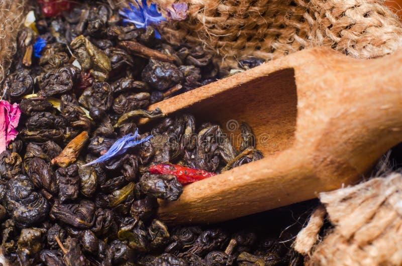 Thé vert dans un sac avec une pelle sur une table en bois images libres de droits