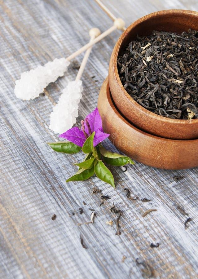Thé vert dans une cuvette en bois avec des fleurs photographie stock libre de droits