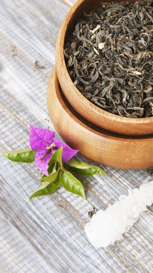 Thé vert dans une cuvette en bois avec des fleurs photos stock
