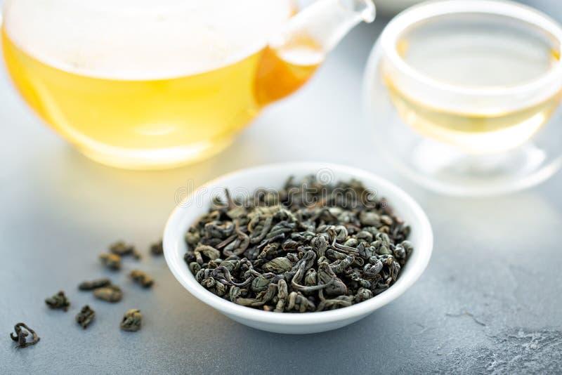 Thé vert de feuilles mobiles et une théière photo stock