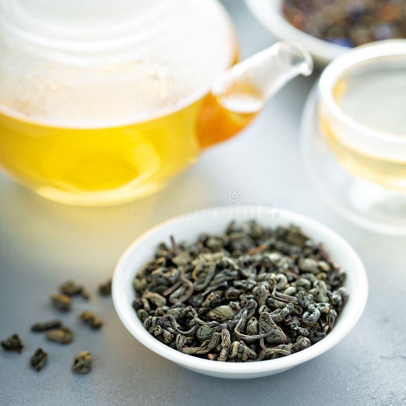Thé vert de feuilles mobiles et une théière photographie stock libre de droits
