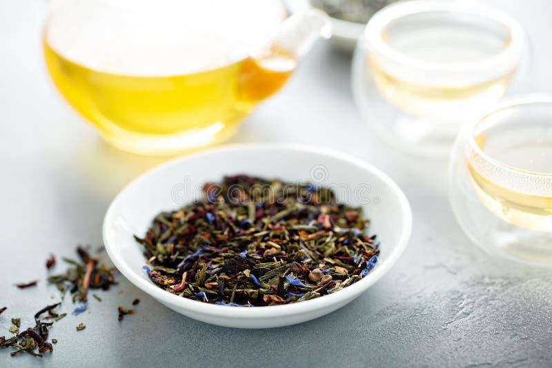 Thé vert de feuilles mobiles et une théière photos libres de droits