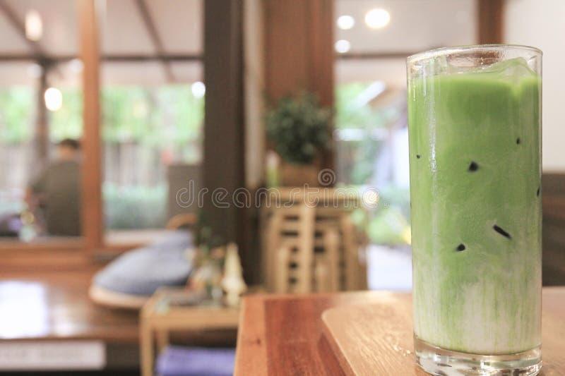 Thé vert de matcha froid de plan rapproché en verre clair placé sur une table en bois photographie stock
