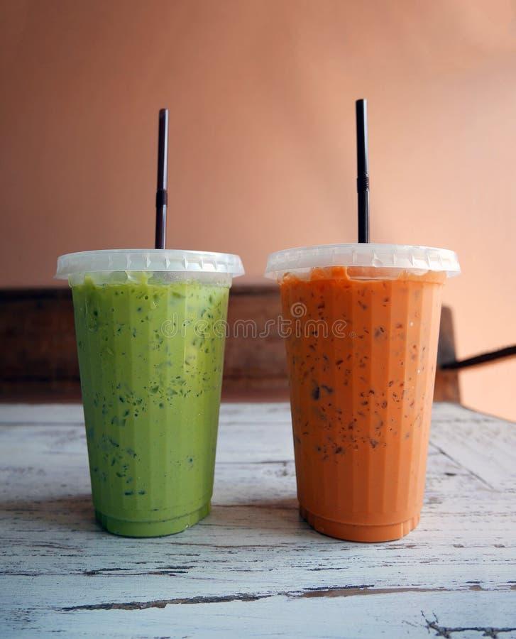 Thé vert glacé et thé de lait d'orange dans des tasses en plastique images libres de droits