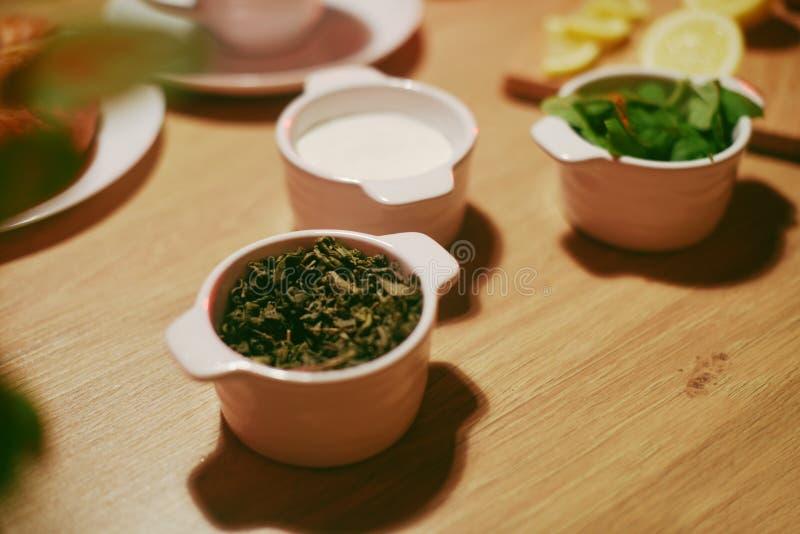 Thé vert, sucre et menthe dans des cuvettes sur une table en bois Thé mariné, feuille de thé de fines herbes image libre de droits