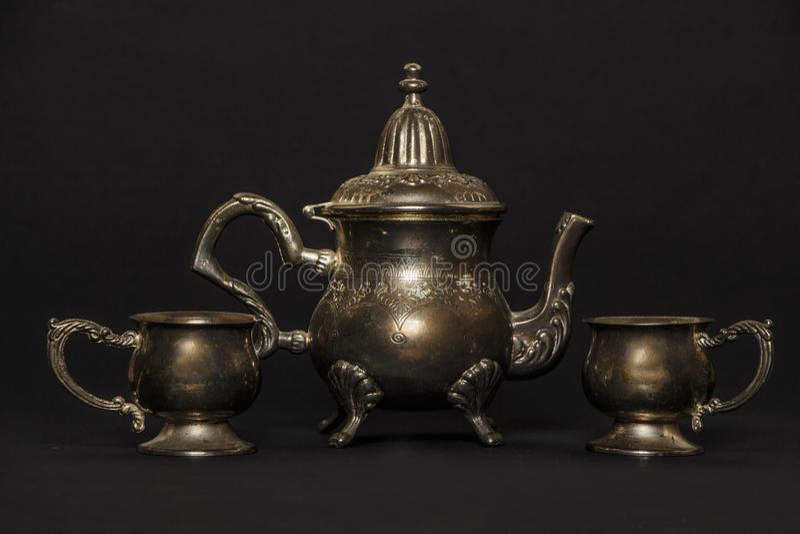 Théière antique argentée sur un fond noir Une belle théière argentée antique La bouilloire est argent image stock