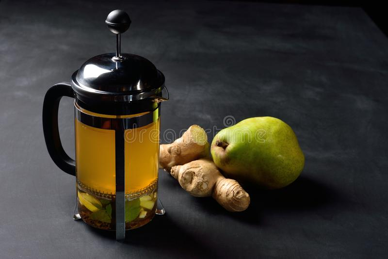 Théière avec le thé et la poire de gingembre sur le fond foncé photos stock