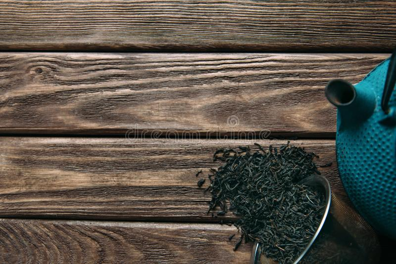 Théière de fer et feuilles de thé sèches images stock