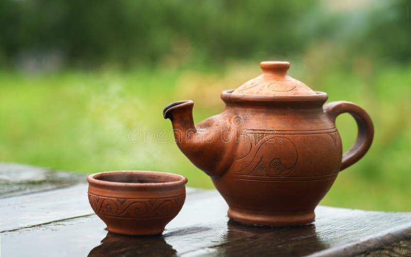 Théière et tasse fabriquées à la main d'argile sur la table en bois extérieure avec le temps pluvieux image stock