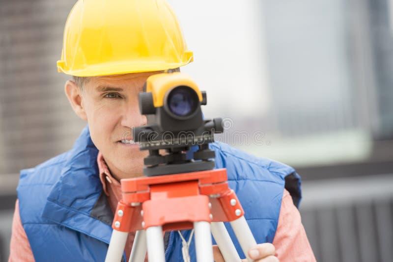 Théodolite de Measuring Distances With de travailleur de la construction images libres de droits