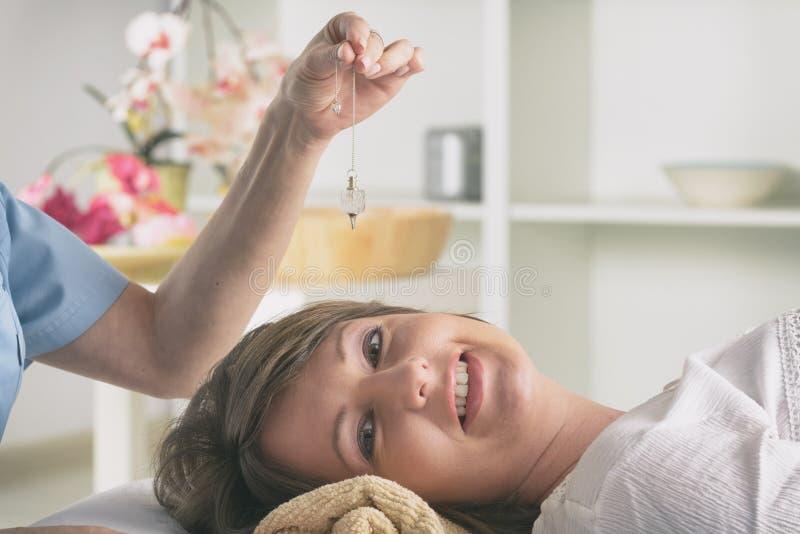 Thérapeute à l'aide du pendule pour faire un diagnostic photo libre de droits