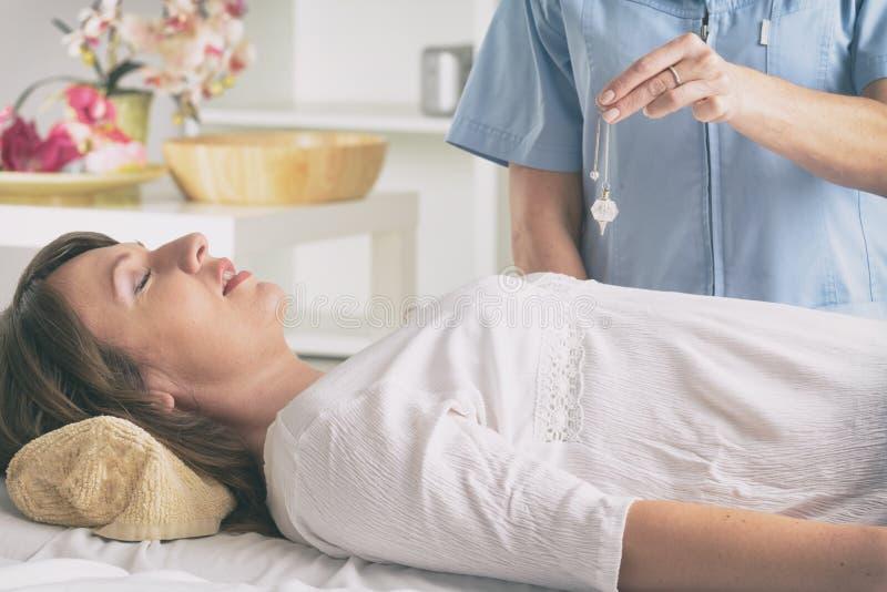 Thérapeute à l'aide du pendule pour faire un diagnostic photos stock