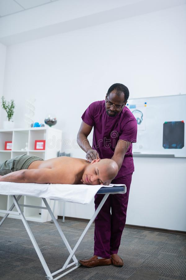 Thérapeute à la peau foncée de massage massant le corps du sportif photo libre de droits