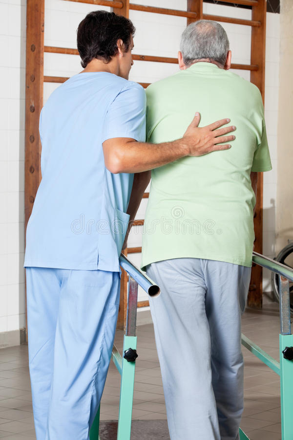 Thérapeute Assisting Senior Man à marcher avec images stock