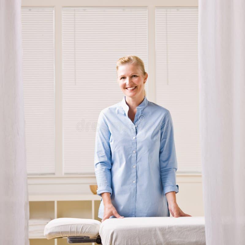 Thérapeute de massage à côté de table de massage image stock