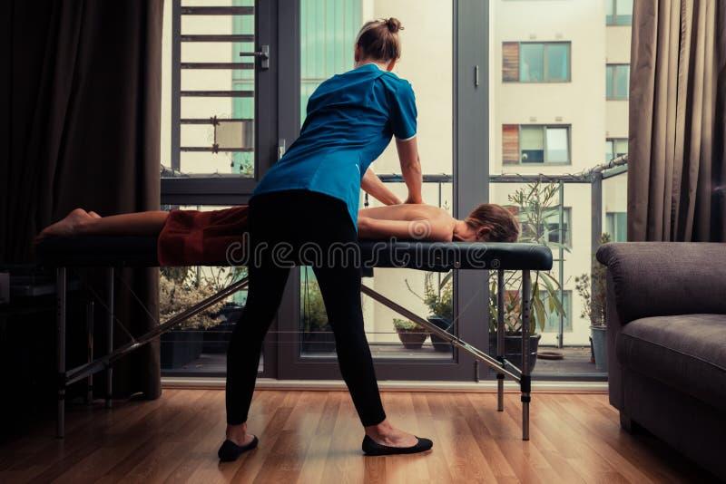 Thérapeute de massage soignant le patient à la maison image libre de droits
