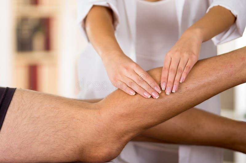 Thérapeute féminin de plan rapproché le physio- remet travailler aux jambes masculines de patients, fond trouble de clinique images stock