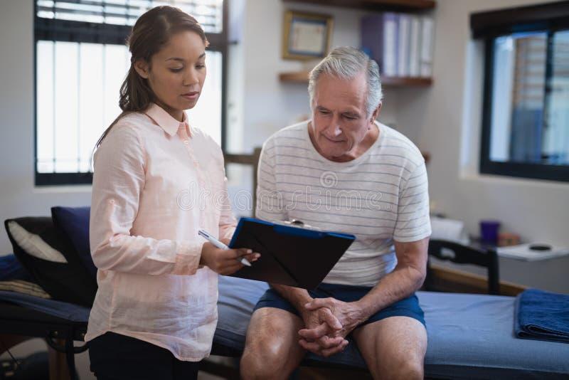 Thérapeute féminin montrant le presse-papiers au patient masculin supérieur s'asseyant sur le lit photos stock