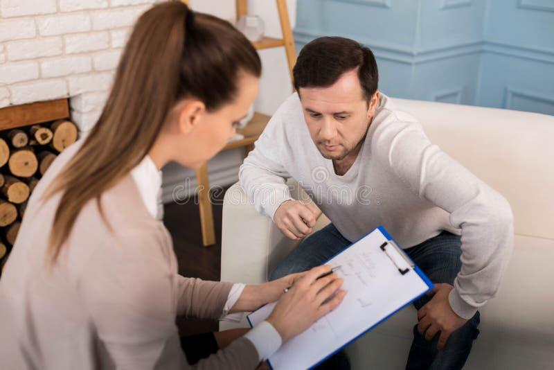 Thérapeute professionnel beau expliquant ses notes photos stock