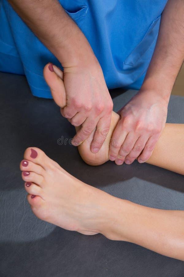 Thérapie de mobilisation d'articulation de la cheville d'homme de docteur à la femme photos libres de droits