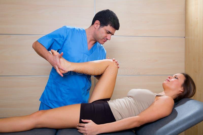 Thérapie de mobilisation de hanche par le thérapeute à la belle femme photo libre de droits