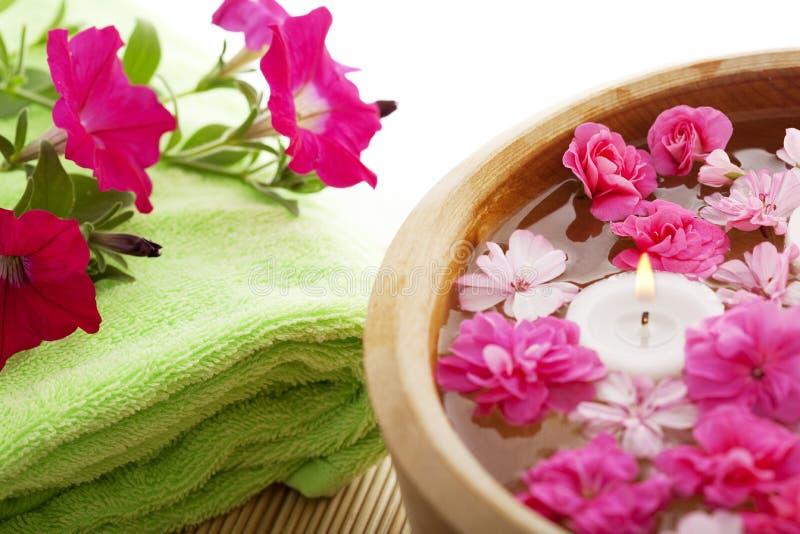 Thérapie de station thermale, fleurs dans l'eau, sur un couvre-tapis en bambou. photo libre de droits