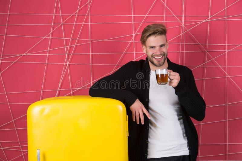 Thés de matin pour sauter le début votre jour Sourire gai d'homme avec la boisson de matin près du réfrigérateur Tasse de prise d image libre de droits