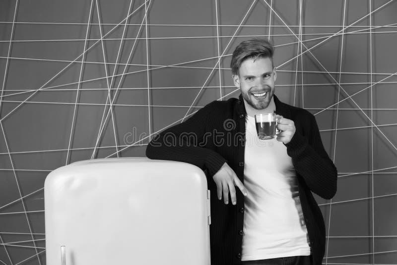 Thés de matin pour sauter le début votre jour Sourire gai d'homme avec la boisson de matin près du réfrigérateur Tasse de prise d photos libres de droits