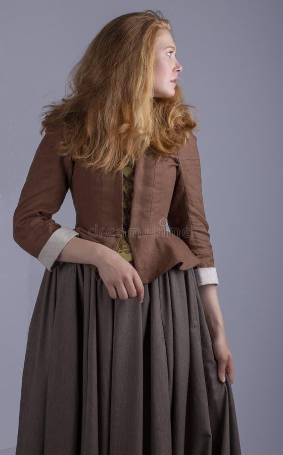 18th århundradekvinna i brun dräkt på den vanliga studiobakgrunden fotografering för bildbyråer