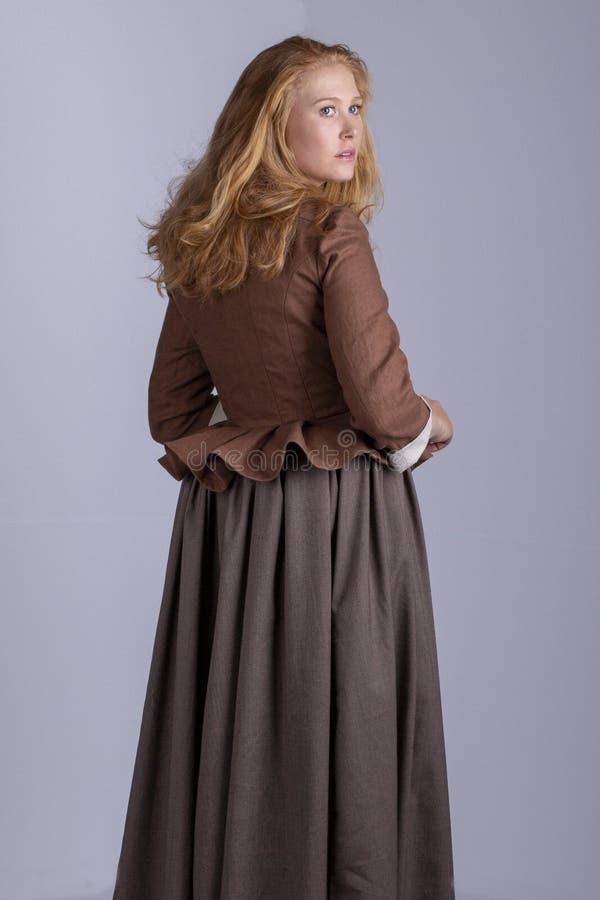 18th århundradekvinna i brun dräkt på den vanliga studiobakgrunden royaltyfri fotografi