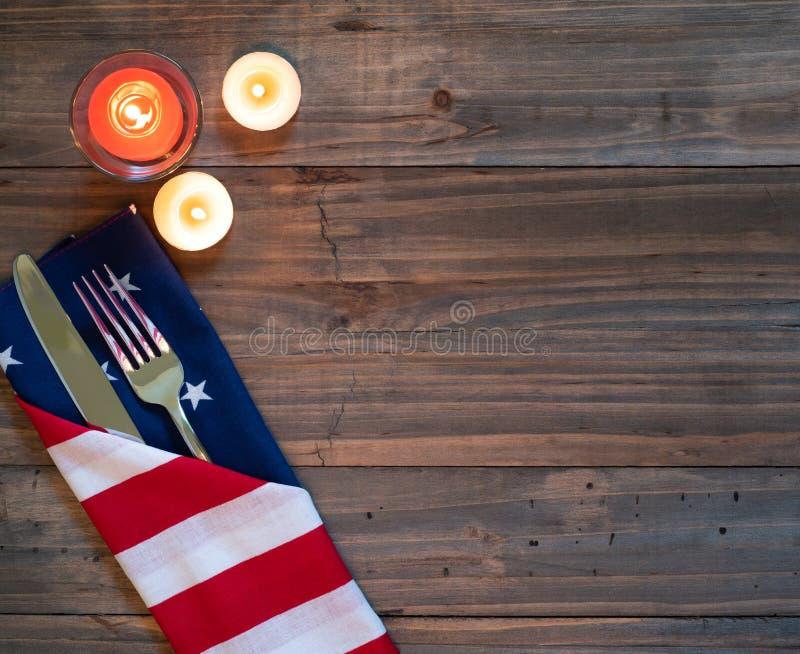 4th av Juli den lantliga tabellen Placesetting med amerikanska flagganservetten, bestick och tre stearinljus på en träbrädebakgru royaltyfria bilder