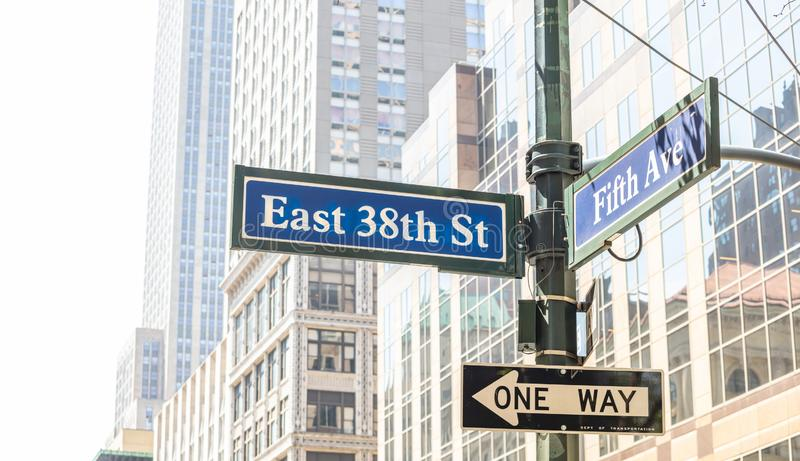 5th ave and E38 corner. Blue color street signs, Manhattan New York downtown. Fifth ave and East 38th crossroads street signs, Manhattan New York downtown. Blur stock image