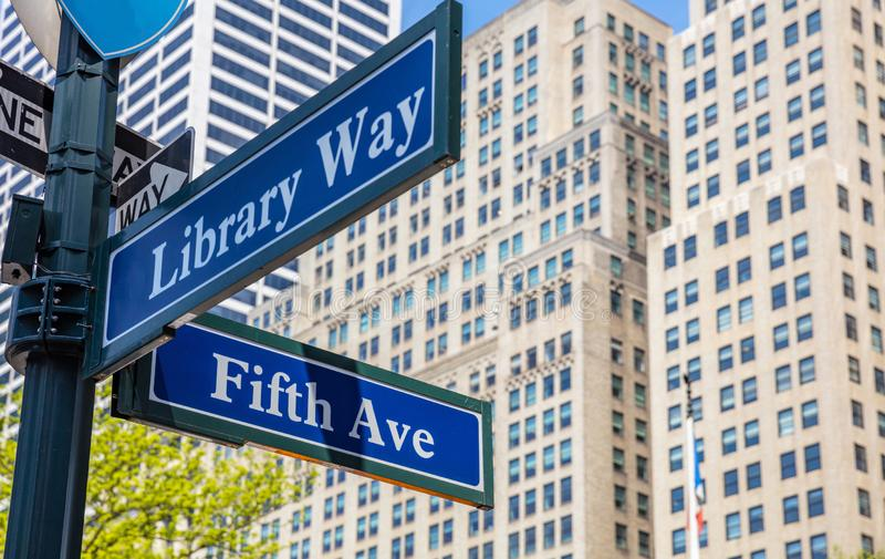 5th ave and Library Way corner. Blue color street signs, Manhattan New York downtown. Fifth ave and Library Way crossroads street signs, Manhattan New York royalty free stock images