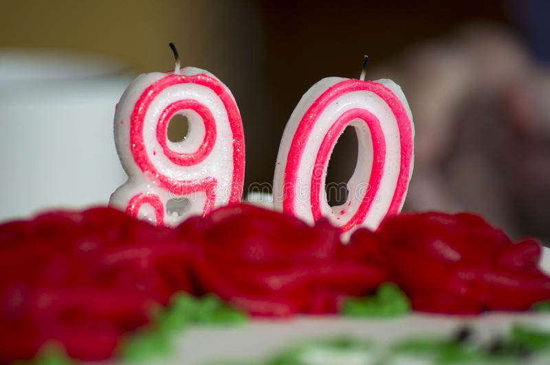 90th Birthday Cake Candles. '90' Candles amongst iced roses on a birthday cake royalty free stock image