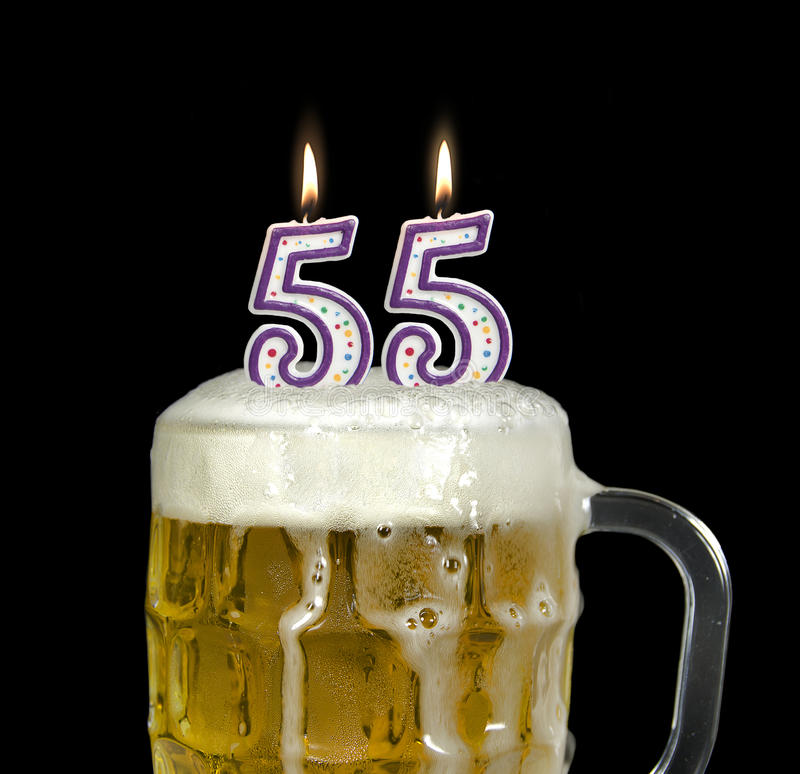 55th birthday candles in beer. Lit birthday candles in a mug of beer for 55th birthday stock photography