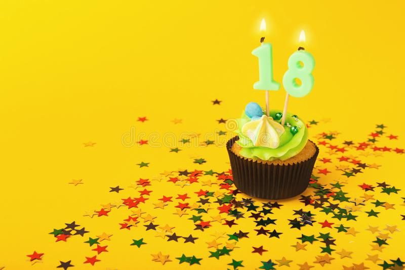 18th birthday cupcake with candle and sprinkles royalty free stock images