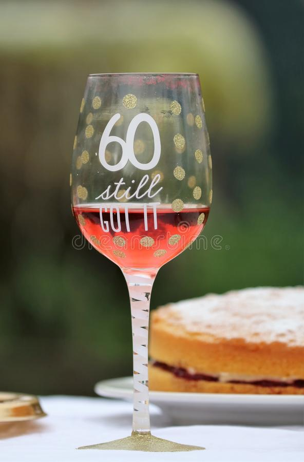 60th birthday wine glass. A glass and cake for celebrating a 60th birthday. Glass with rose wine and 60 still got it royalty free stock photos