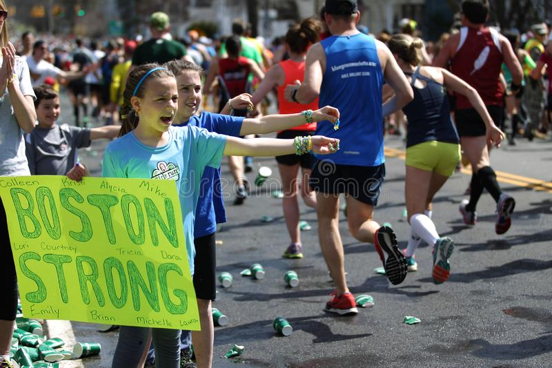 118th Boston Marathon took place in Boston, Massachusetts, on Monday, April 21 Patriots` Day 2014. Children spectators offer rings to runners royalty free stock photo