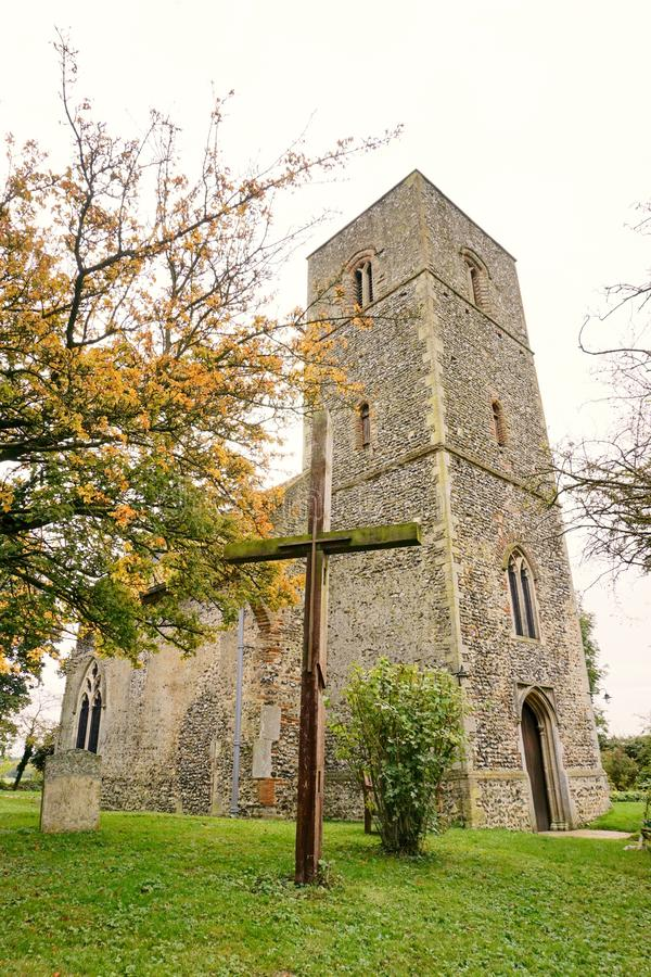 Ancient church. St Mary's church at Houghton-on-the-hill in Norfolk. Pictured here with a wooden cross outside the church dates from the 11th century. It stock photo