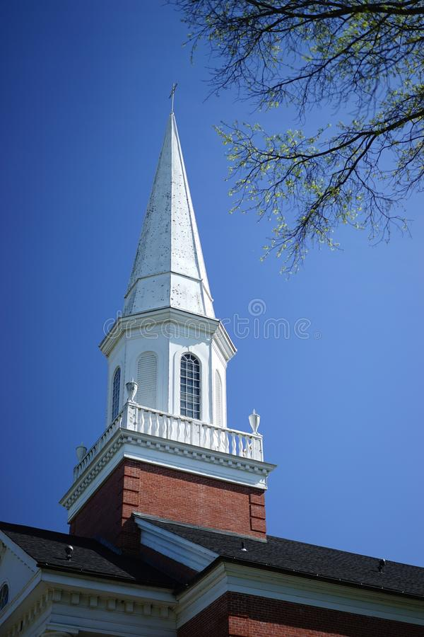 19th century church steeple in early morning sun. This church steeple is surrounded by a parapet with decorative architectural urns royalty free stock images