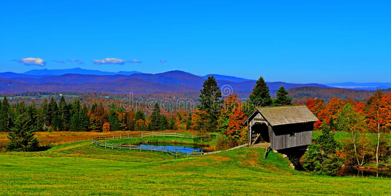 19th Century covered bridge in rolling green mountains of Vermont HDR. royalty free stock photography