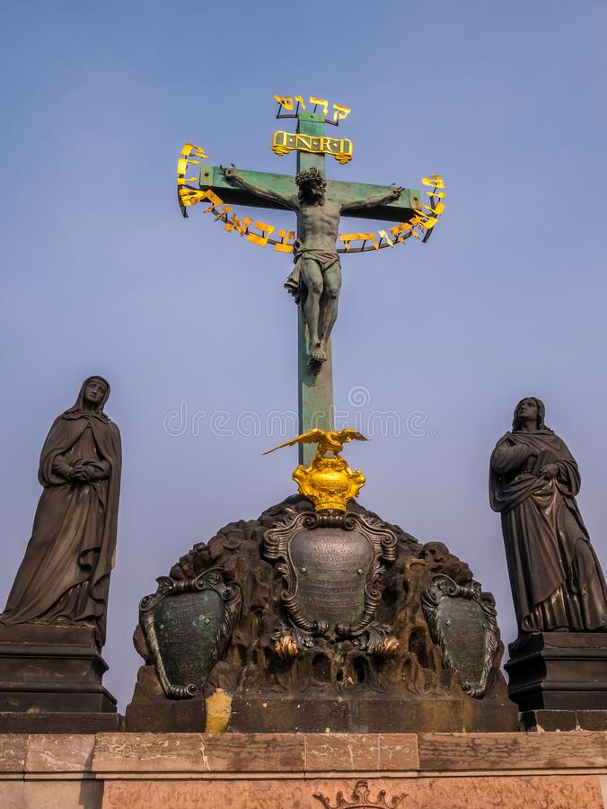 17th Century Crucifixion statue with Hebrew lettering blue sky in Charles Bridge Prague, Czech Republic . royalty free stock image