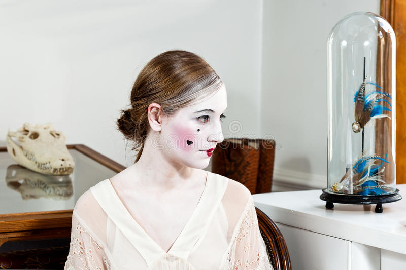 18th century enlightment make-up girl. Girl with 18th century Parisian Versailles style make-up and with alligator skull and blue feathers in the background royalty free stock photography
