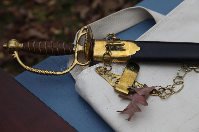 18th century still life sword and scabbard. 18th century still life of a sward and scabbard lying on a table in the autumn. Revolutionary war stock images